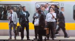 Business men yawning on the subway platform in Tokyo at night Stock Footage