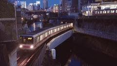 Train lines converge at Ochanomizu Station, Tokyo, at night - stock footage