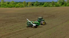Agriculture tractor sowing seeds and cultivating field in late afternoon - stock footage