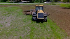 Tractor harrowing the large brown field in spring season Stock Footage