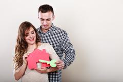 Stock Photo of Couple with paper house. Housing real estate.