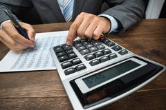 Close-up Of Businessperson Doing Calculation With Calculator In Office Stock Photos