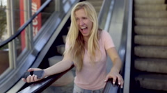 Girl Spins On Escalators, She Gets Stuck Between Them, Laughs Hysterically Stock Footage