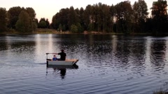 A man with his son in a small canoe across the calm waters of Coquitlam lake. Stock Footage