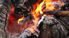 Ashes and flame on burning log in a fire Stock Footage