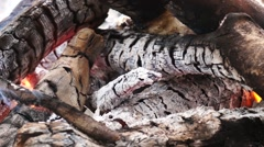 Ashes and flame on burning log in a fire - stock footage