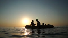 Children playing with rubber boat with sunset in background - stock footage