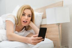 Astonished Young Woman In Bed Holding Mobile Phone Stock Photos