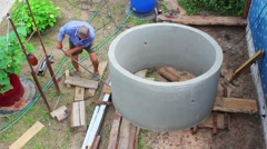 Stock Video Footage of Man working building constructing concrete cylinder alone manually