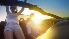 Timelapse of couple driving convertible cabriolet car with sunset sun Stock Footage