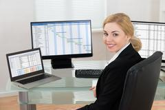 Happy Businesswoman On Office Chair Working At Computers Stock Photos