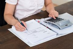 Female Accountant Calculating Bills With Calculator In Office - stock photo