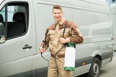 Young Male Worker With Pesticide Standing Near The Van - stock photo