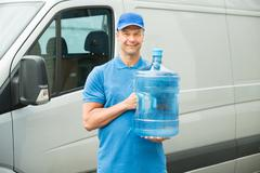 Happy Delivery Man Holding Water Bottle In Front Of Truck - stock photo