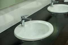 white basins in bathroom interior with granitic tiles. - stock photo