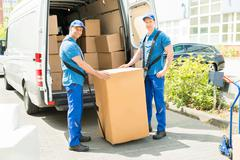 Two Happy Movers In Blue Uniform Loading Boxes In Truck Stock Photos