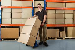Happy Male Worker With Boxes On Hand Truck In Large Warehouse Stock Photos