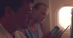 Young people using tablet PC and cell phone in plane - stock footage