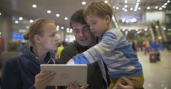Parents and child with pad at the crowded airport Stock Footage