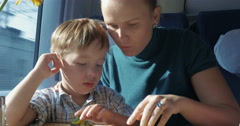 Son and mother with pictured book in train Stock Footage