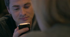 Young man with pleased smile texting on cell phone - stock footage