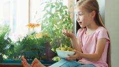 Girl sitting on a windowsill and eating gooseberries. Zooming Stock Footage