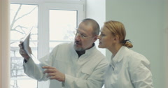 Two doctors comparing x-ray images Stock Footage