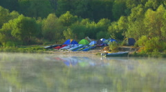 Picturesque water surface with vapor and sport boat camp on the river bank Stock Footage
