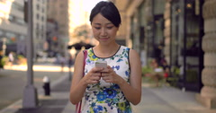 Young Asian woman walking texting cell phone Stock Footage