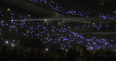 Crowd on stands waving flashlights at night Stock Footage