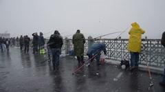 Fishermen fishing under snow, commuters walking, Galata, Istanbul Arkistovideo