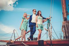 Stylish wealthy friends on a luxury yacht Stock Photos