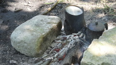 Two blackened camp kettles on stone fire, water boiling Stock Footage