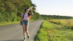 Beautiful young girl hitchhiking travels Stock Footage