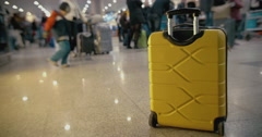 Yellow suitcase on the floor at crowded airport Stock Footage