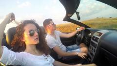 Young Caucasian couple fun driving luxury cabriolet convertable car. SLOW MOT Stock Footage