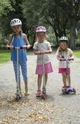 Three children riding scooters in a New York park USA - stock photo
