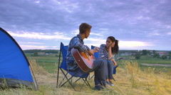 Couple sit near bonfire and camping tent: man play the guitar, woman listen Arkistovideo