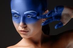 Portrait of a woman who is posing covered with blue paint Stock Photos