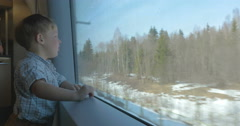 Boy looking at nature scene through the train window Stock Footage