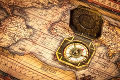 Vintage pirate retro compass on ancient world map - stock photo