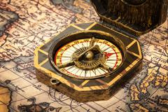 Vintage pirate retro compass close up on ancient world map - stock photo