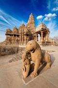 King and lion fight statue and Kandariya Mahadev temple.  Khajuraho, India - stock photo