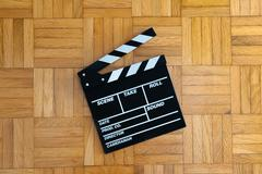 Movie clapper board on wooden floor Stock Photos