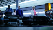 Stock Video Footage of TL out of focus airport passeners at baggage col 4K