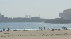People on the beach and a cargo ship floating on Atlantic ocean, Porto Stock Footage