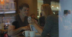 Young people using smart phone and talking in cafe Stock Footage