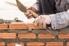 Bricklayer working in construction site of a brick wall - stock photo