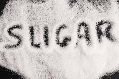 The word sugar written into a pile of white granulated sugar Stock Photos