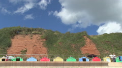 Promenade Beach Huts and Red Cliffs at Seaton in Devon Stock Footage